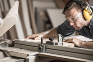 Young attractive man doing woodwork in carpentry